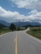 View down a paved highway with mountains on horizon