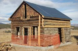 Snair  log cabin with safety fencing around front half of building