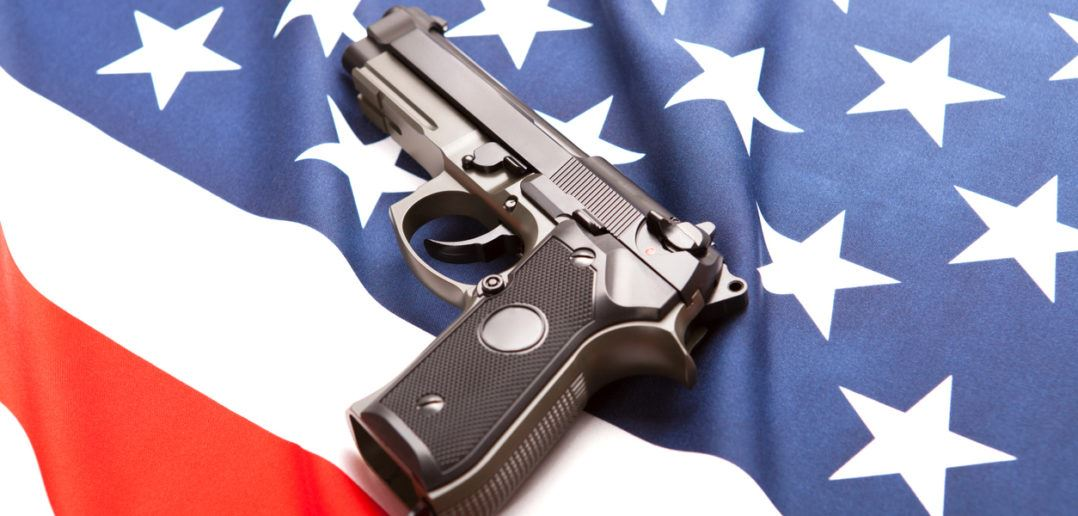 American Flag with a gun laying on top